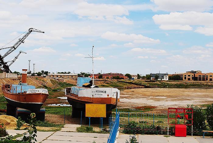 Wybrzeże Aralska (Kazachstan), kutry rybackie i fabryki w oddali. Tylko gdzie jest morze???