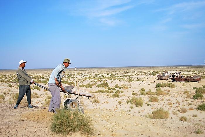 Robotnicy na tle kutrów i dna Morza Aralskiego – Moynaq (Uzbekistan)