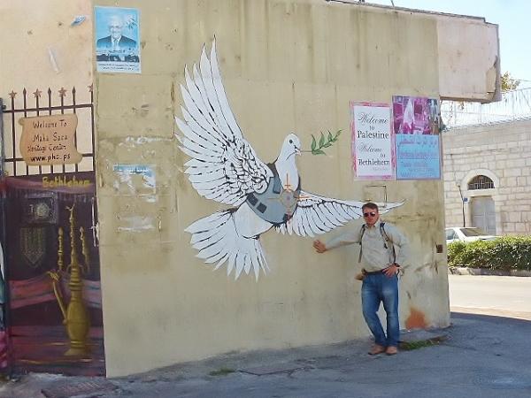 """Betlejem - jeden z wielu palestyńskich rysunków na ścianach zwanych """"banksy"""". Na tym zdjęciu widzimy białego gołębia symbolizującego Palestynę, który ma na sobie kamizelkę kuloodporną, gałązkę oliwną w dziobie oraz celownik wycelowany w serce przez izraelskiego snajpera. Obraz ten symbolizuje Palestyńczyków jako ludzi pokoju będących pod żydowskim zaborem. Żydzi kwestionują wiarygodność tego obrazu mówiąc, że Palestyńczycy nie chcą pokoju lecz lubią udawać pokojowych. Ocenę zostawiam moim czytelnikom."""