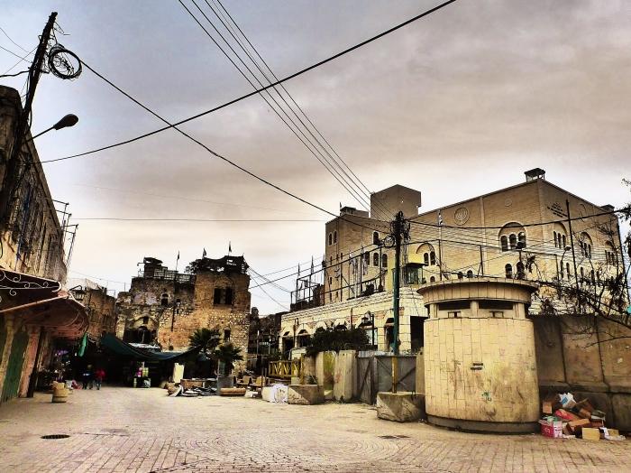 Baza wojskowa Izraela przez wejściem do Starego Miasta w Hebron. Proszę zwrócić uwagę na budki snajperów na dachu po obu stronach budynku oraz miejscami dla żółnierzy z karabinami maszynowymi za siatką. Wraz z przemieszczaniem się naprzód jest o wiele więcej takich niespodzianek.