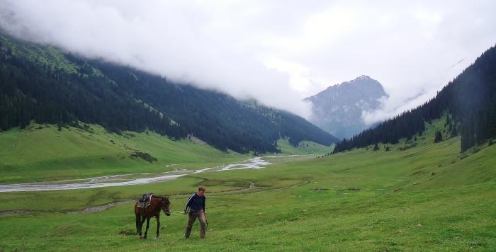 Idę z moim koniem przez góry, niedaleko Altyn Arashan w Kirgistanie.